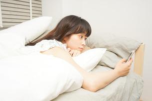 寝る前に携帯を使う若い女性の写真素材 [FYI04665842]