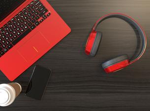 メタリックレッドのヘッドフォンとノートパソコンの写真素材 [FYI04665850]