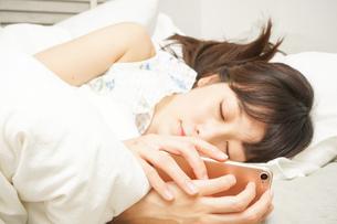 寝る前に携帯を使う若い女性の写真素材 [FYI04665857]