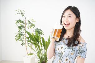 部屋でビールを飲む若い女性の写真素材 [FYI04665878]