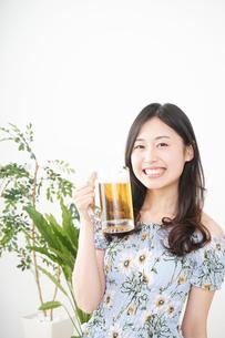 部屋でビールを飲む若い女性の写真素材 [FYI04665879]