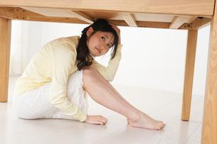 地震から身を守る女性の写真素材 [FYI04665897]