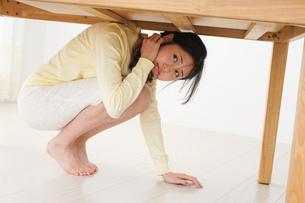 地震から身を守る女性の写真素材 [FYI04665905]
