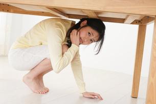 地震から身を守る女性の写真素材 [FYI04665908]