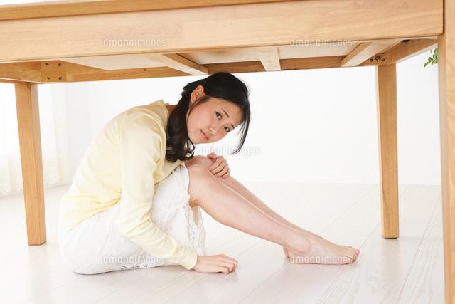 地震から身を守る女性の写真素材 [FYI04665909]