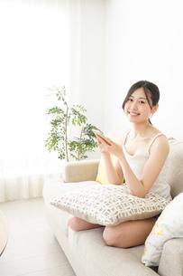 部屋でスマホを使う若い女性の写真素材 [FYI04665921]