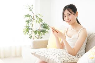 部屋でスマホを使う若い女性の写真素材 [FYI04665934]