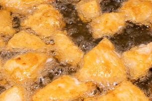 【料理】チキンナゲットを油で揚げる様子の写真素材 [FYI04666480]