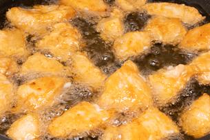 【料理】チキンナゲットを油で揚げる様子の写真素材 [FYI04666481]