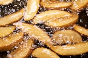 【料理】フライドポテトを油で揚げる様子の写真素材 [FYI04666482]