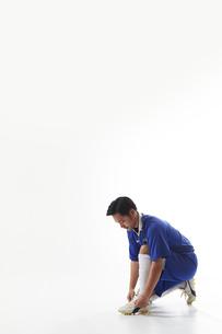 スパイクの紐を結ぶサッカー選手の写真素材 [FYI04666648]