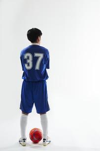 サッカーボールの前で腕組みをするサッカー選手の後ろ姿の写真素材 [FYI04666651]