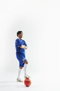 手を腰に当ててサッカーボールに片足を乗せる選手の写真素材 [FYI04666652]