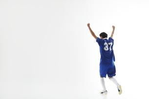 万歳をしながら小走りをするサッカー選手の写真素材 [FYI04666661]