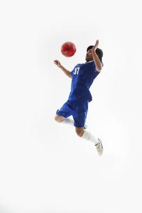 ジャンプして胸トラップをするサッカー選手の写真素材 [FYI04666674]