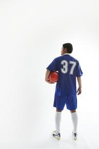 片手でボールを抱えるサッカー選手の後ろ姿の写真素材 [FYI04666688]