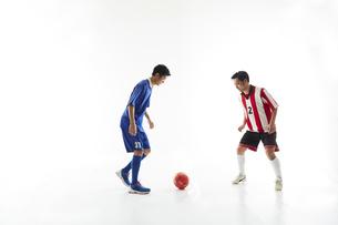 サッカーの試合でボールを蹴る人と守る人の写真素材 [FYI04666738]