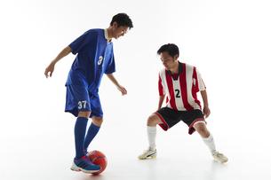 サッカーの試合でボールを蹴る人と守る人の写真素材 [FYI04666739]