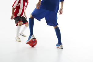 サッカーの試合でボールを蹴る人と守る人の写真素材 [FYI04666740]