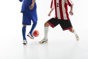 サッカーの試合でボールを蹴る人と守る人の写真素材 [FYI04666741]