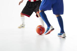 サッカーの試合でボールを蹴る人と守る人の足の写真素材 [FYI04666744]