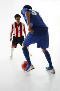サッカーの試合でボールを蹴る人と守る人の写真素材 [FYI04666745]