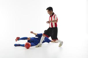 サッカーの試合でボールを蹴る人と守る人の写真素材 [FYI04666746]