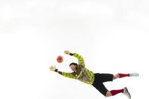 飛び出してボールを掴もうとするゴールキーパーの写真素材 [FYI04666753]