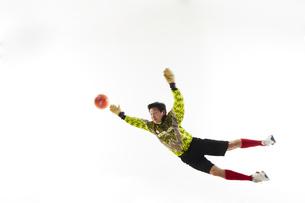 飛び出してボールを掴もうとするゴールキーパーの写真素材 [FYI04666758]
