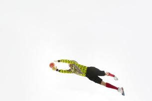 飛び出してボールを掴もうとするゴールキーパーの写真素材 [FYI04666762]
