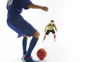 サッカーの試合でボールを蹴る人とゴールキーパーの写真素材 [FYI04666778]