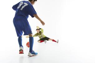 サッカーの試合でボールを蹴る人とゴールキーパーの写真素材 [FYI04666780]