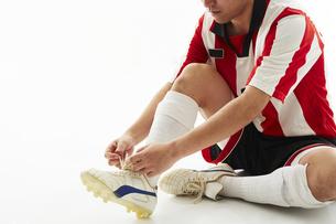 スパイクの紐を結ぶサッカー選手の写真素材 [FYI04666951]