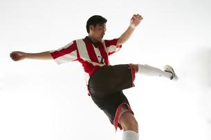 ボールを蹴り足を振りかぶるサッカー選手の写真素材 [FYI04666960]