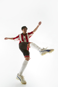 ボールを蹴り足を振りかぶるサッカー選手の写真素材 [FYI04666963]