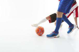 相手のボールをスライディングでカットするサッカー選手の写真素材 [FYI04666966]