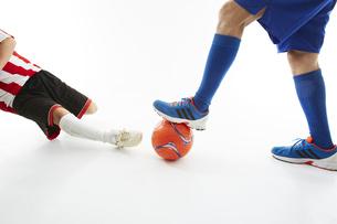 相手のボールをスライディングでカットするサッカー選手の写真素材 [FYI04666971]