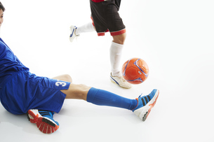 相手のボールをスライディングでカットするサッカー選手の写真素材 [FYI04666973]