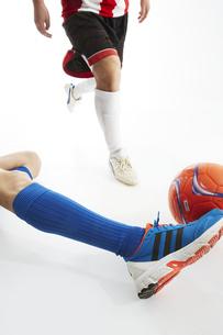 相手のボールをスライディングでカットするサッカー選手の写真素材 [FYI04666974]