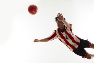 飛び込んでヘディングをする瞬間のサッカー選手の写真素材 [FYI04666989]