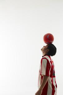 額の上でボールのバランスをとるサッカー選手の写真素材 [FYI04666990]