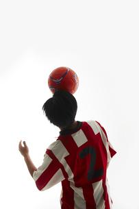 額の上でボールのバランスをとるサッカー選手の写真素材 [FYI04666991]