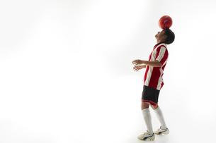 額の上でボールのバランスをとるサッカー選手の写真素材 [FYI04666992]