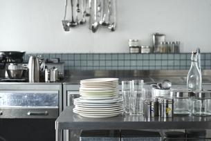 タイルとステンレスキッチンの上に置かれたキッチン雑貨の写真素材 [FYI04667157]