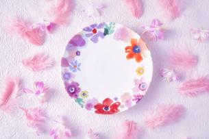 ピンクの和紙の上に置かれた花柄の皿とピンクの羽や花の写真素材 [FYI04667182]