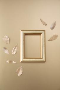 ゴールドで統一された背景と額と葉型の小物の写真素材 [FYI04667186]