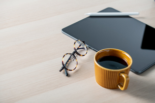 Digital tablet on table with stylus pen,cup of coffee,eyeglasses. Technology lifestyle image.の写真素材 [FYI04667407]
