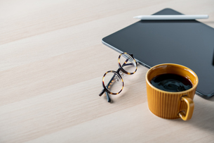 Digital tablet on table with stylus pen,cup of coffee,eyeglasses. Technology lifestyle image.の写真素材 [FYI04667408]