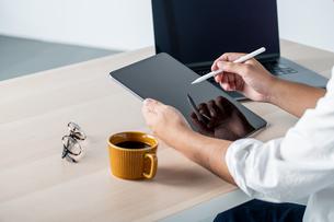 Man using stylus pen for digital tablet.の写真素材 [FYI04667435]
