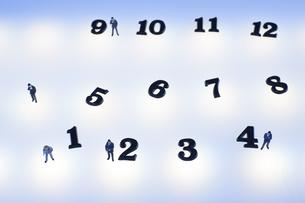 複数の光の中の数字とミニチュアの人のシルエットの写真素材 [FYI04667522]